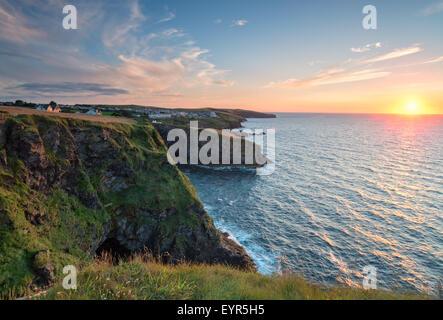 Coucher de soleil depuis les falaises de Port Gaverne sur la côte nord des Cornouailles robuste Banque D'Images
