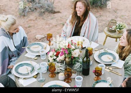 Un petit groupe de femmes bénéficiant d'un repas en plein air dans un désert.