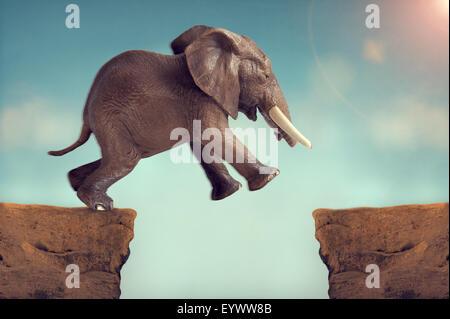 Acte de foi sur un saut éléphant concept crevasse Banque D'Images