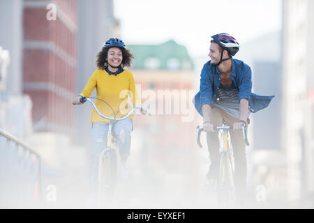 Jeune couple riding bicycles in city Banque D'Images