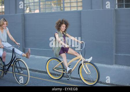 Les femmes espiègles sur les bicyclettes de cabotage vers le bas de la rue en milieu urbain Banque D'Images