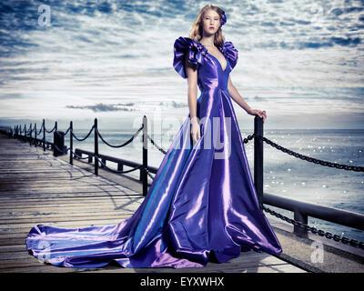 Jeune femme portant une belle et longue robe de soirée bleu debout à bord de l'eau, fashion portrait artistique Banque D'Images