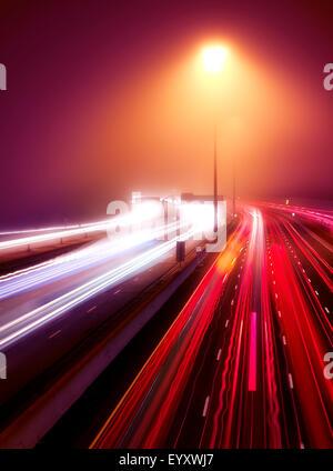 Route passante feu sentiers dans le cadre d'une nuit brumeuse, l'autoroute 401, Toronto, Ontario, Canada.
