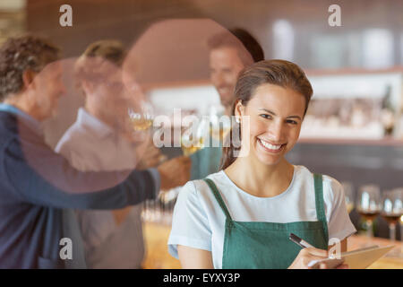Portrait smiling worker with clipboard in winery salle de dégustation Banque D'Images