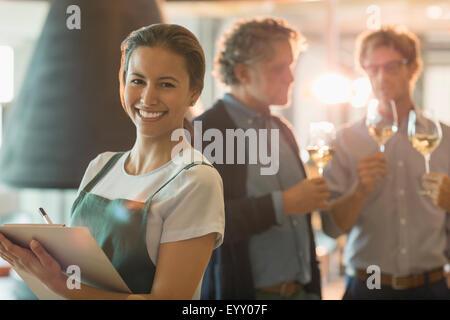 Portrait of smiling woman with clipboard travaillant dans la salle de dégustation de vin Banque D'Images