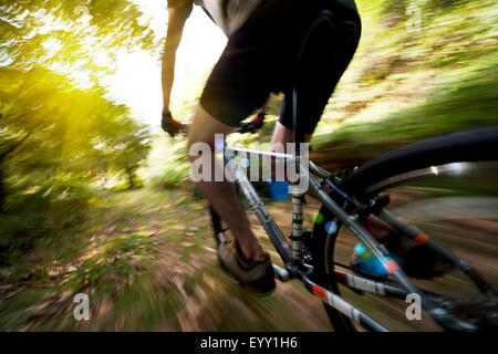 Blurred view of Caucasian man riding dirt bike in forest