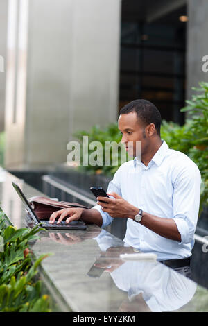 Black businessman using laptop and cell phone outdoors Banque D'Images