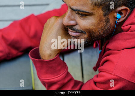 Close up of mixed race man listening to oreillette Banque D'Images