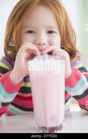 Young Girl blowing bubbles en lait fraise Banque D'Images