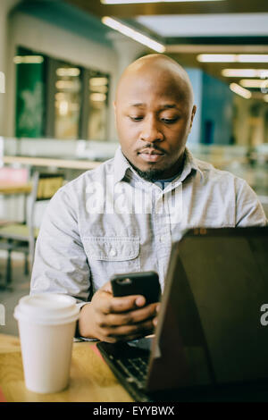 Black businessman using cell phone in cafe Banque D'Images