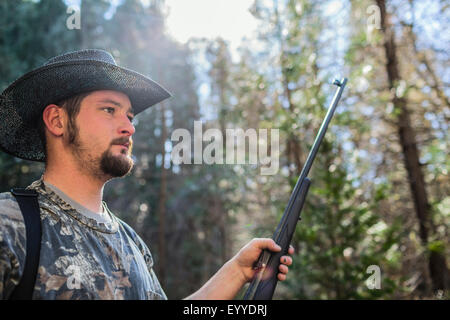 Young hunter holding gun in forest Banque D'Images