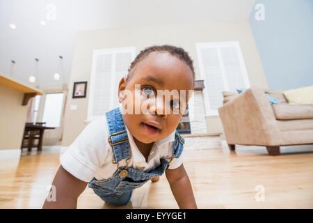 Black baby crawling sur plancher du salon Banque D'Images
