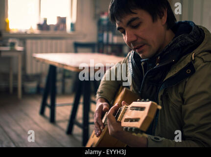 Asian man playing guitar in living room Banque D'Images