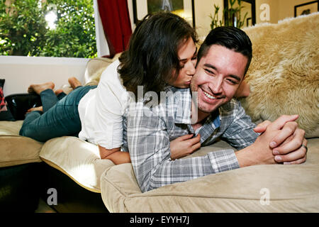 Couple relaxing on sofa in living room Banque D'Images