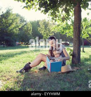 Les jeunes mères et jeunes enfants élégant livre de lecture au jardin en été fun Banque D'Images