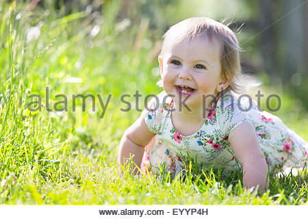 Portrait of smiling baby crawling on grass Banque D'Images