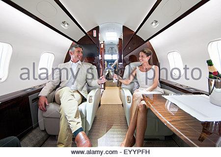 Smiling couple faire un toast avec du champagne en jet privé Banque D'Images