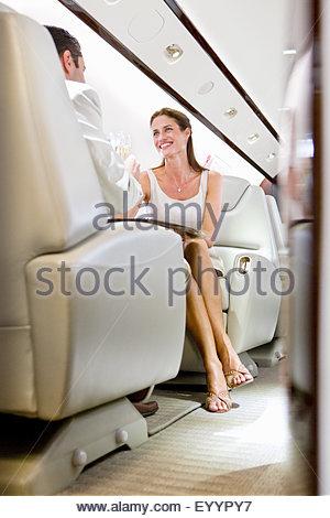 Smiling couple attrayant de faire un toast avec du champagne sur jet privé Banque D'Images