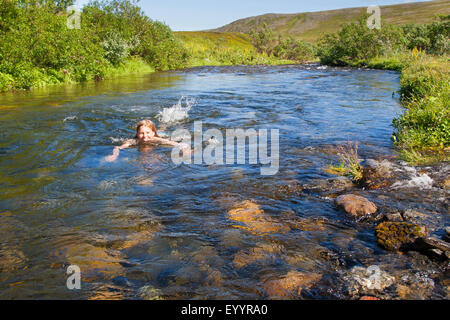 Girl baignade dans une crique, Allemagne Banque D'Images
