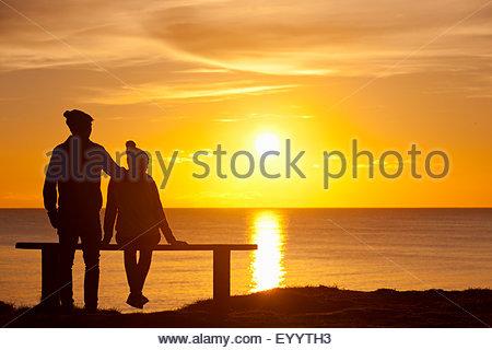 Silhouette de couple, sur un banc, contre le coucher du soleil sur l'océan Banque D'Images