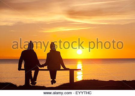 Silhouette de couple, assis sur un banc, tenant les mains, contre le coucher du soleil sur l'océan Banque D'Images