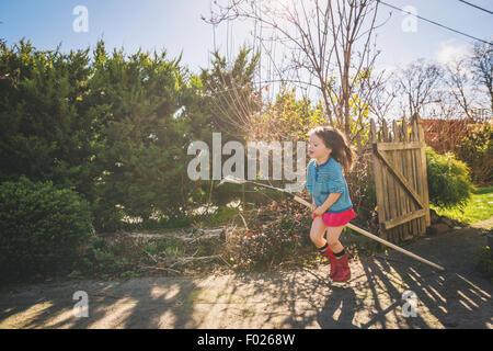 Young Girl riding râteau dans yard comme c'est un cheval Banque D'Images
