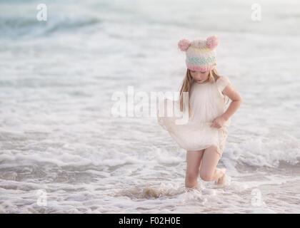 Fille dans une robe courant dans l'océan surf, Californie, États-Unis