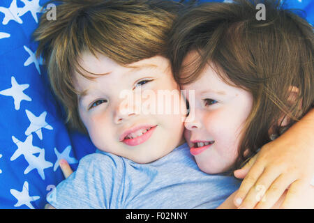 Deux enfants allongés sur une couverture serrant les uns les autres Banque D'Images
