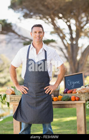 Smiling farmer standing with hands on hips Banque D'Images