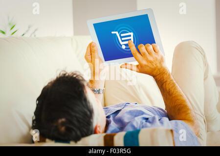 Image composite de l'homme portant sur canapé à l'aide d'un tablet pc Banque D'Images