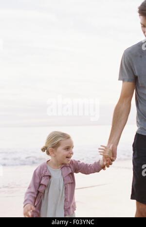 Homme debout sur une plage de sable fin à l'océan, tenant la main de sa jeune fille. Banque D'Images