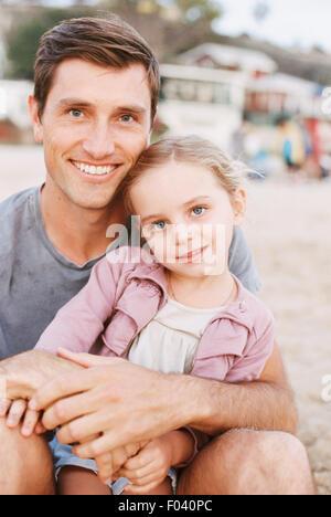 Jeune fille assise sur les genoux de son père, looking at camera, souriant. Banque D'Images