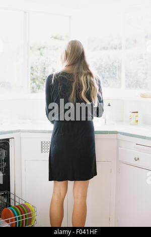 Vue arrière d'une femme avec de longs cheveux blonds debout à un évier de cuisine. Banque D'Images