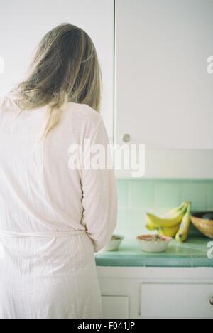 Vue arrière d'une femme debout dans une cuisine, préparer le petit-déjeuner. Banque D'Images