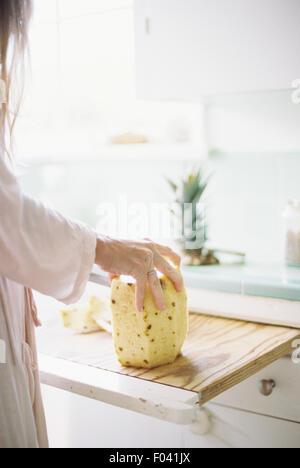 Femme debout dans une cuisine, découpage d'un ananas frais. Banque D'Images