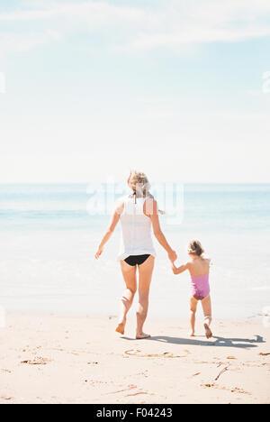 Femme jouant avec sa fille sur une plage de sable. Banque D'Images