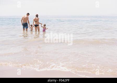 Couple avec leur fils et leur fille, un comité permanent de la famille dans les eaux peu profondes au large de la Banque D'Images