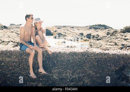 Un homme et une femme, en couple sur la plage assis sur un mur d'une piscine dans les rochers. Banque D'Images