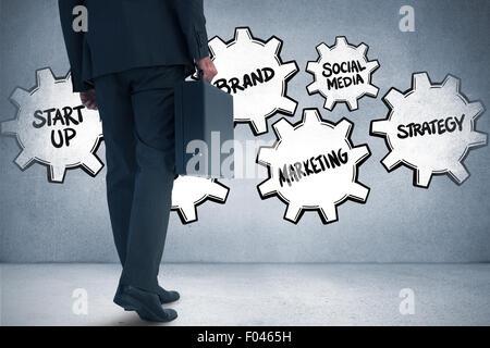 Composite image of businessman holding briefcase walking