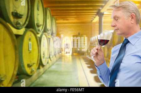 Man smelling red wine in cellar Banque D'Images
