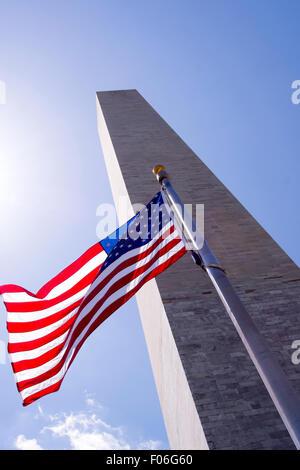 Washington Monument et US flag against blue sky