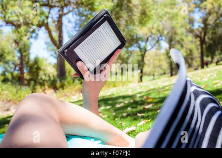 Une femme dans un parc de lire un livre sur un e-reader Banque D'Images