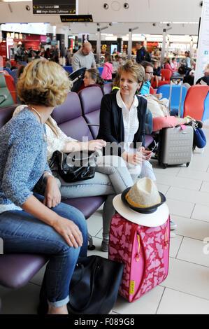Women chatting à heureux dans la salle de départ de l'aéroport de Gatwick South Terminal aller en vacances ensemble Banque D'Images