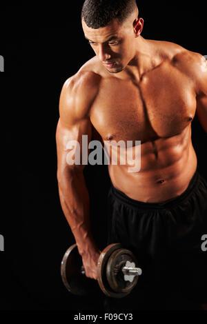 Muscular young man working out avec haltères lourds Banque D'Images