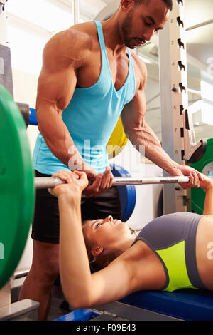 Woman lifting weights avec l'aide de formateurs, side view Banque D'Images