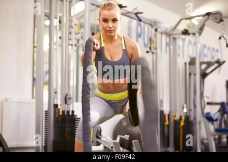 Jeune femme travaillant avec des cordes de combat dans une salle de sport Banque D'Images