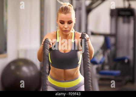Jeune femme se préparent à travailler avec des cordes de combat dans une salle de sport Banque D'Images