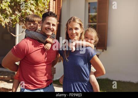 Tourné en plein air d'un couple heureux avec leurs enfants sur leur dos. Portrait d'une mère et père de donner leurs Banque D'Images