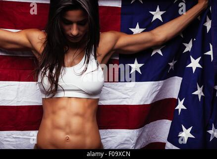 Athlète féminin holding drapeau américain à la recherche vers le bas. Santé de la jeune femme portant des vêtements Banque D'Images