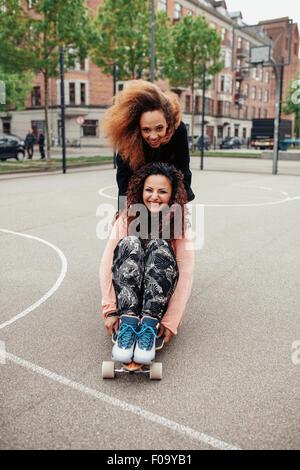 Les filles sur skateboards Hipster équitation le long de la route. Deux jeunes femmes patinage. Femme poussant son Banque D'Images